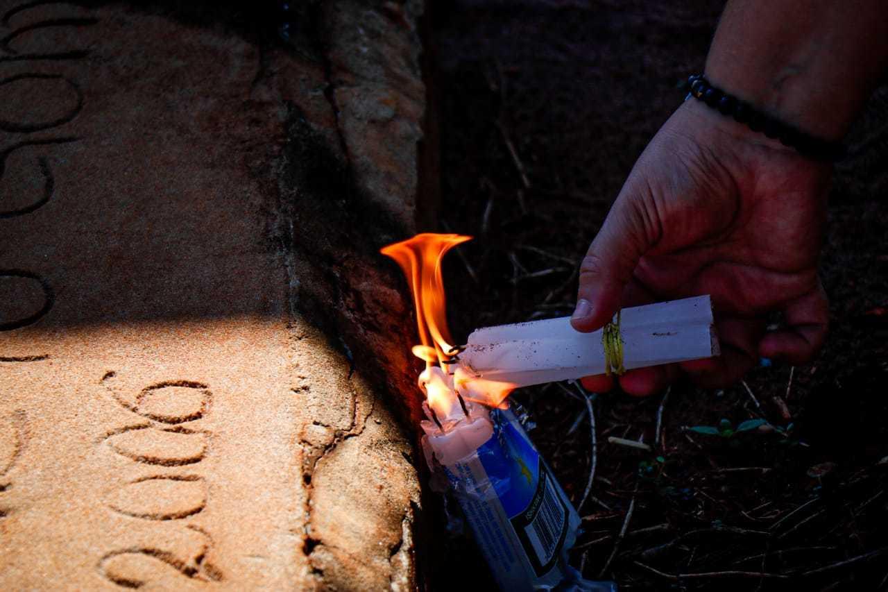 Vela sendo acendida em túmulo de cemitério na Capital. (Foto: Henrique Kawaminami)