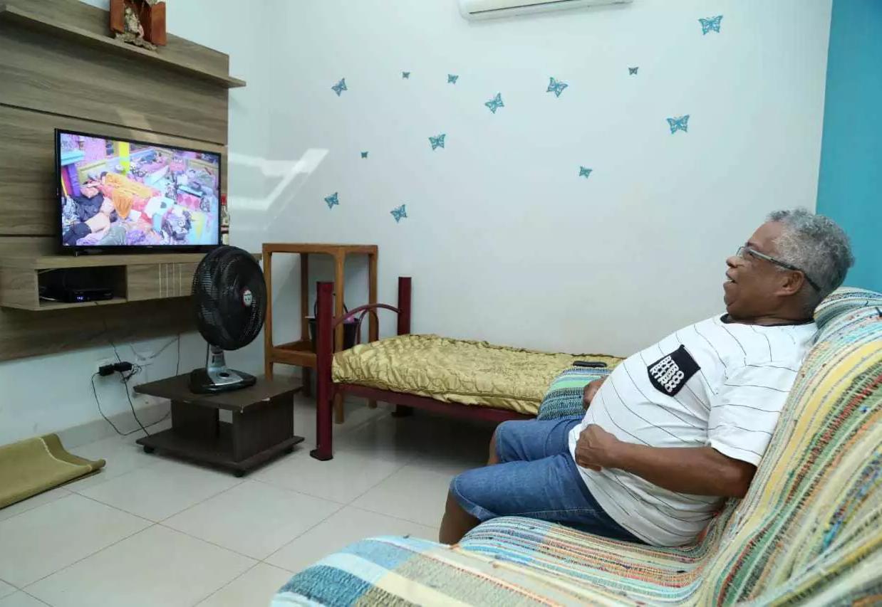 Enesio, em sua casa no Residencial Oliveira, acompanhando o filho Projota via paperview (Foto: Kísie Ainoã)