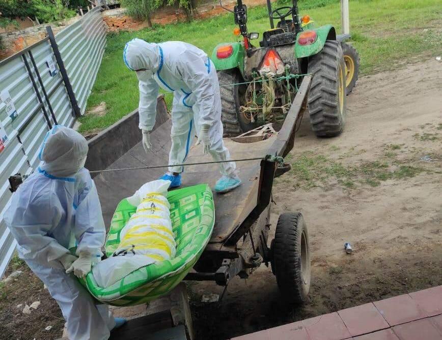 Funcionários de hospital colocam corpo de indigente em carreta de trator (Foto: ABC Color)