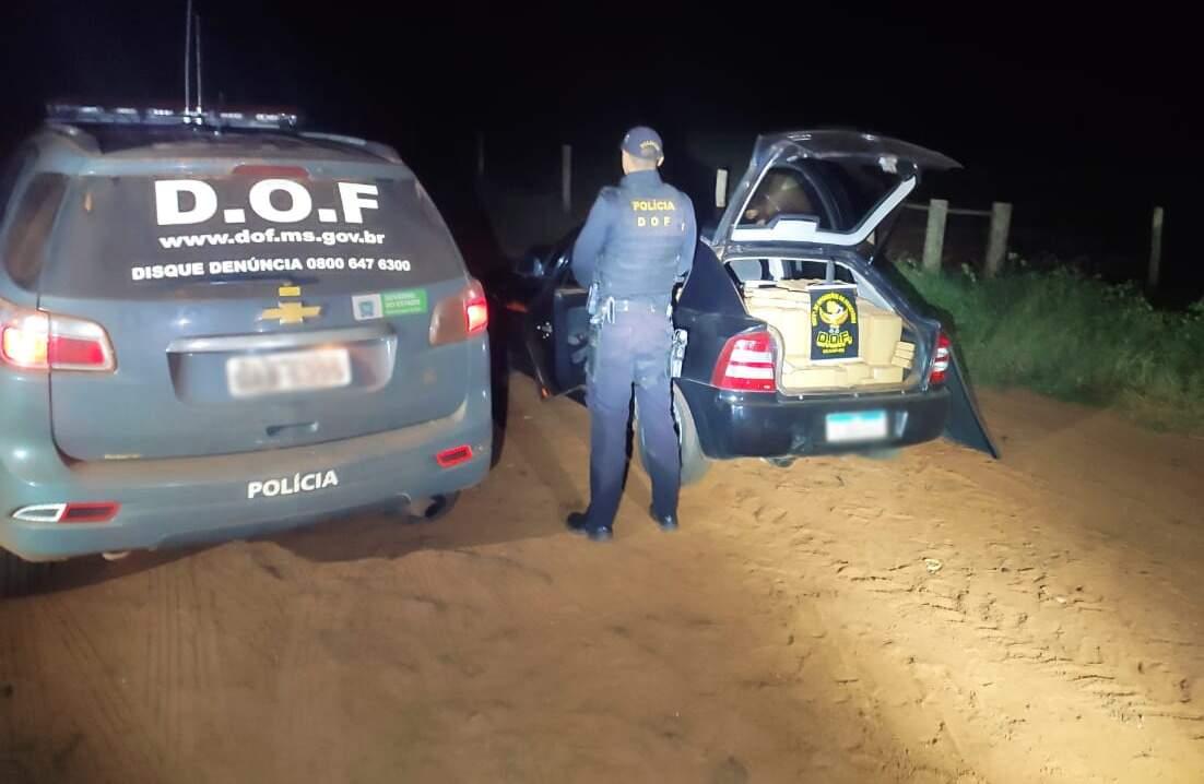 Policial do DOF parado ao lado de Astra com maconha (Foto: Divulgação)