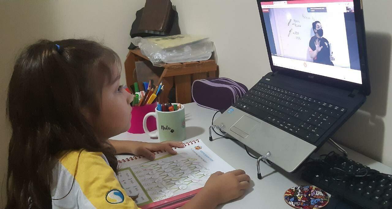 Valentina participa das aulas on-line interagindo com as professoras em frente do PC (Foto: Arquivo Pessoal)