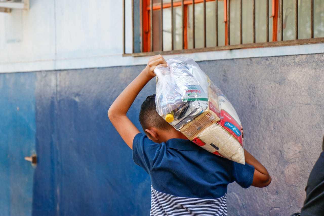 Jovem carrega cesta básica em Campo Grande (Foto: Henrique Kawaminami/Arquivo)