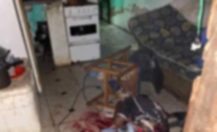 Uma das vítimas caída dentro da residência após ser baleada. (Foto: Direto das Ruas)