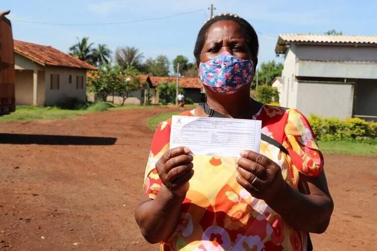 Dona Isaulda exibindo comprovante da primeira dose da vacina contra a covid-19. (Foto: Divulgação)