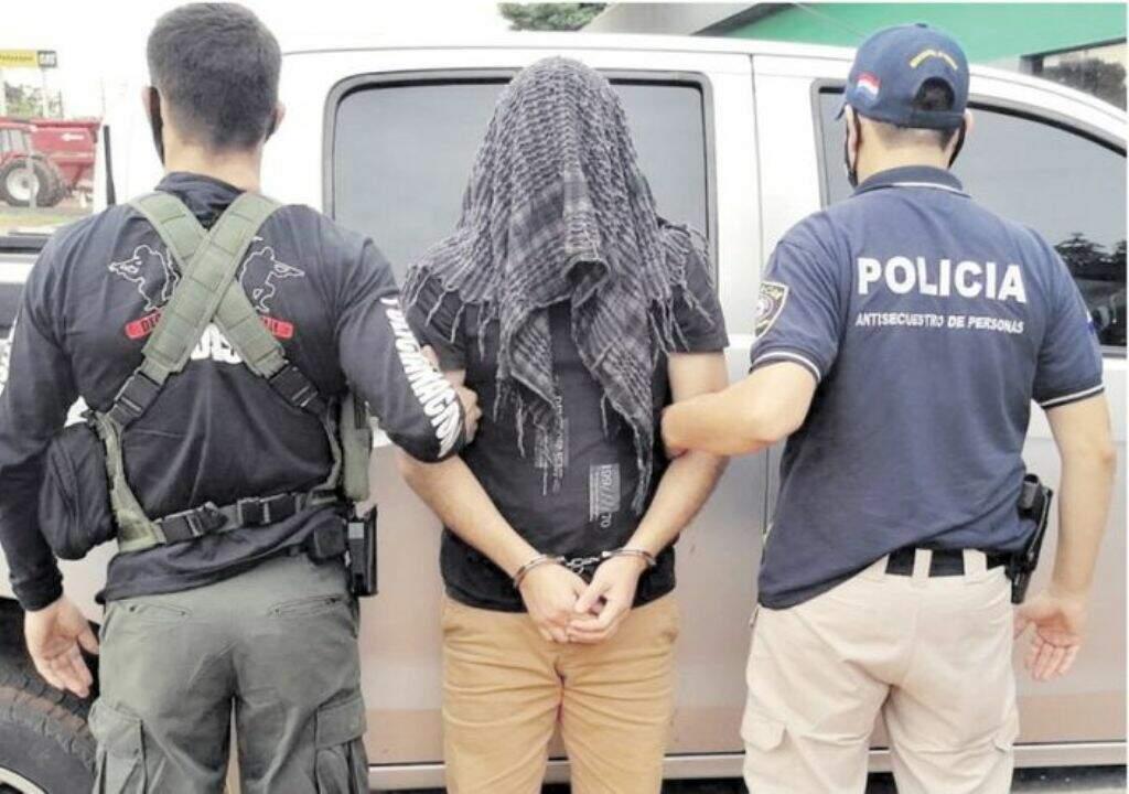 Comerciante de Salto del Guairá com cabeça coberta entre policiais paraguaios (Foto: ABC Color)