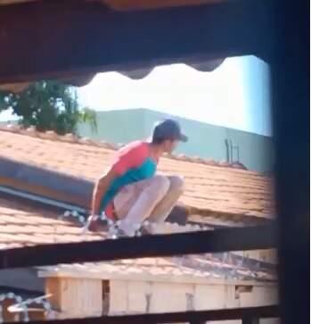 Em cima de telhado, suspeito observa movimentação ao redor. (Foto: Direto das Ruas)
