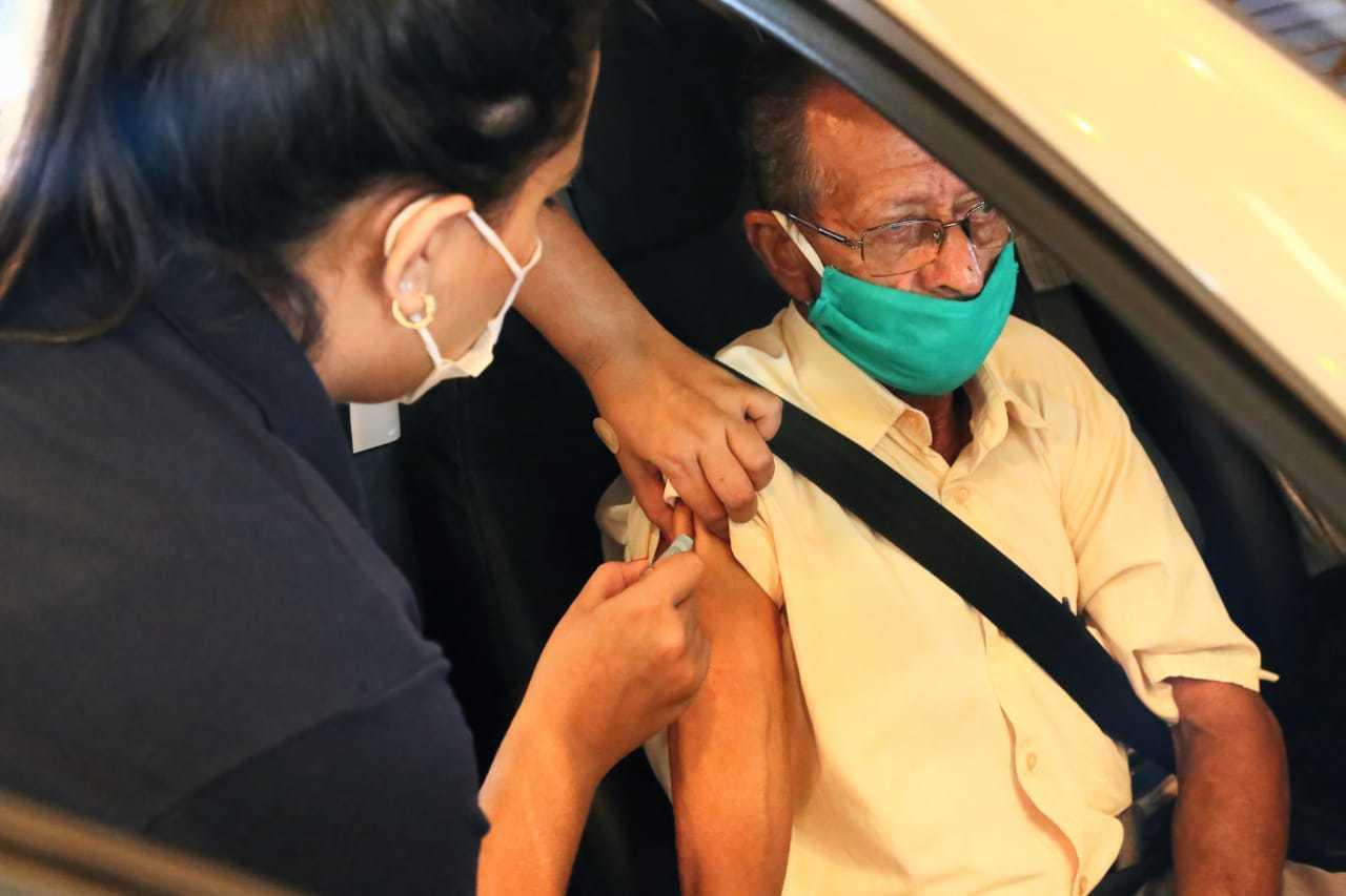 Idoso recebendo dose da vacina em ponto de vacinação em Campo Grande. (Foto: Kísie Ainoã)