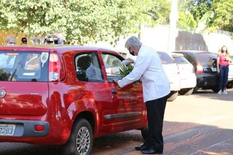 Com 35 litros de água benta, fiéis são ungidos em drive no Domingo de Ramos