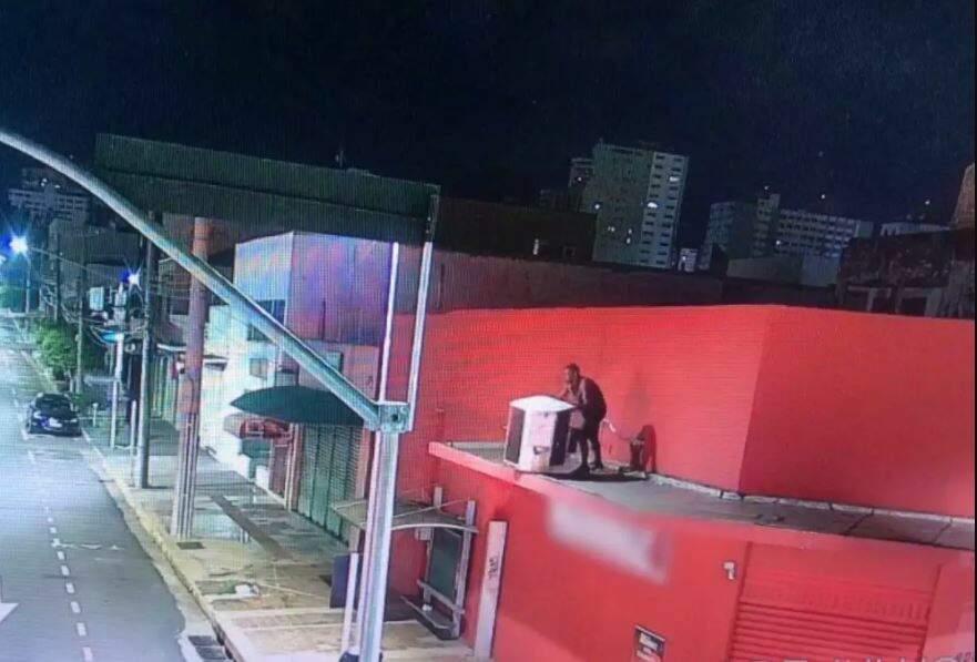 Na marquise, ladrão furta condensador de ar condicionado e é flagrado pelas câmeras de monitoramento. (Foto: Reprodução)