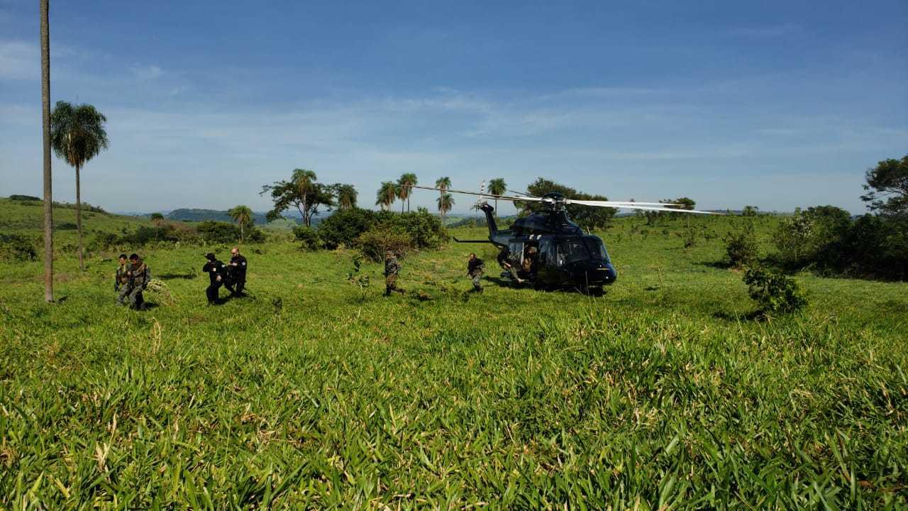 Agentes paraguaios descem de helicóptero brasileiro em área de cultivo de maconha (Foto: Senad)