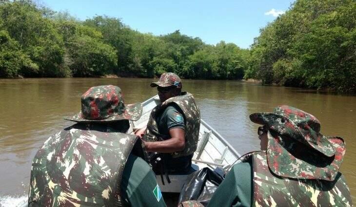 Três agentes da Polícia Militar Ambiental fiscalizando rio de barco. (Foto: Divulgação)