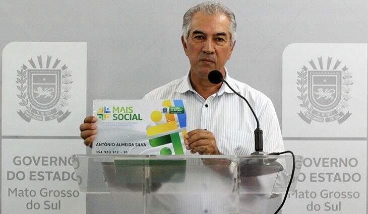 Governador Reinaldo Azambuja (PSDB) mostra replica de como será o cartão do Programa Mais Social (Foto: Divulgação)