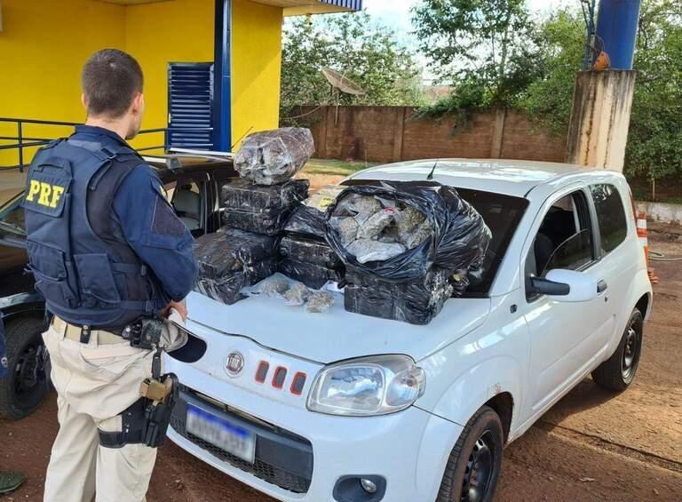 Policial diante do veículo e maconha apreendidos na ação. (Foto: PRF)