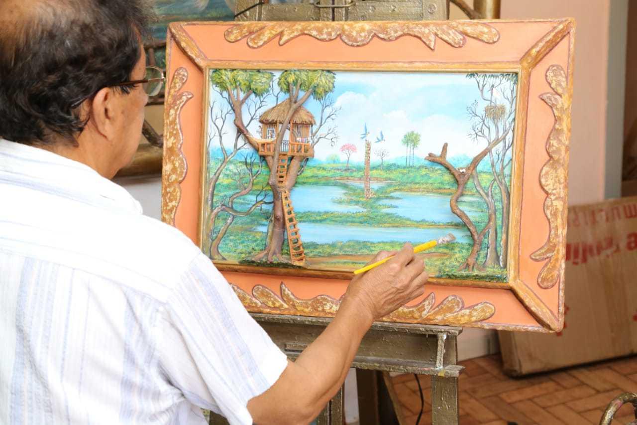 Artista concentrado durante execução de tela em seu ateliê (Foto: Kísie Ainoã)