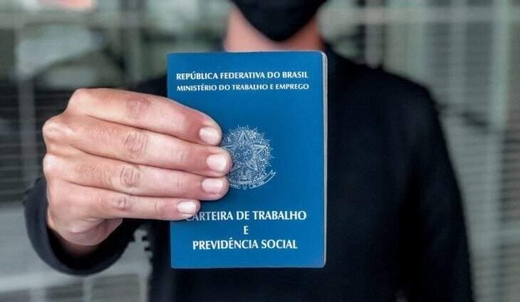 Trabalhador com uma carteira de trabalho em mãos. (Foto: Funtrab)