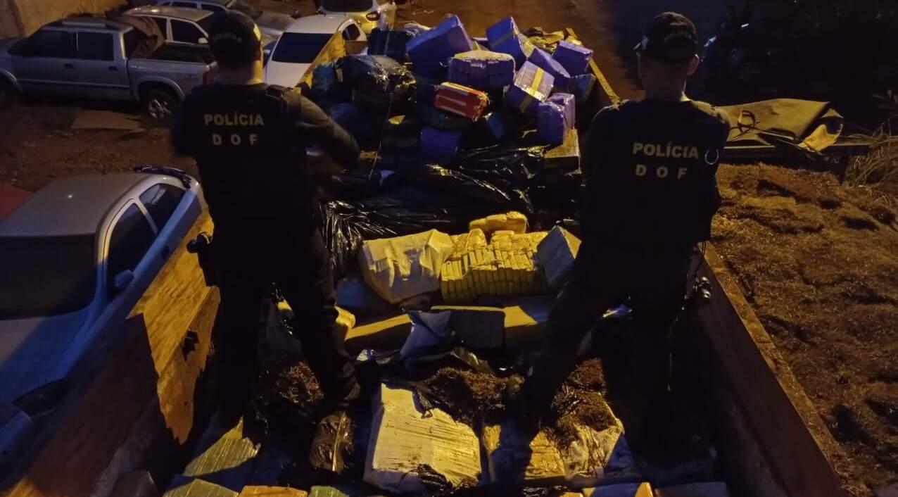 """Policiais sobre os fardos de maconha após descarregarem os """"tabletes"""" de grama. (Foto: DOF)"""