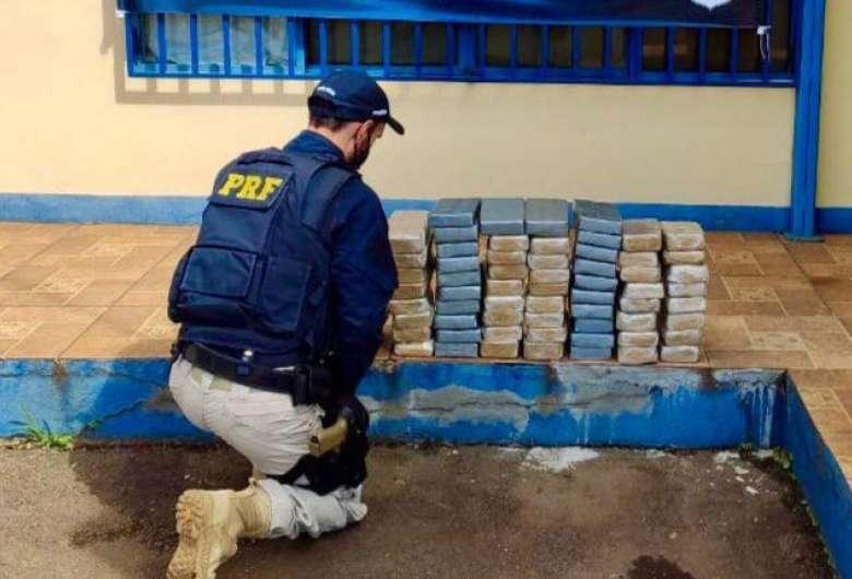 Policial de frente com os tabletes da droga. (Foto: Dourados News)