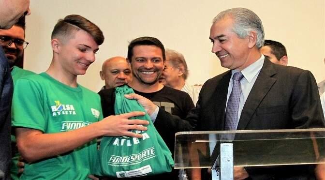 Kawãh recebendo do governador Reinaldo Azambuja kit do Bolsa Atleta. (Foto: Fundesporte)