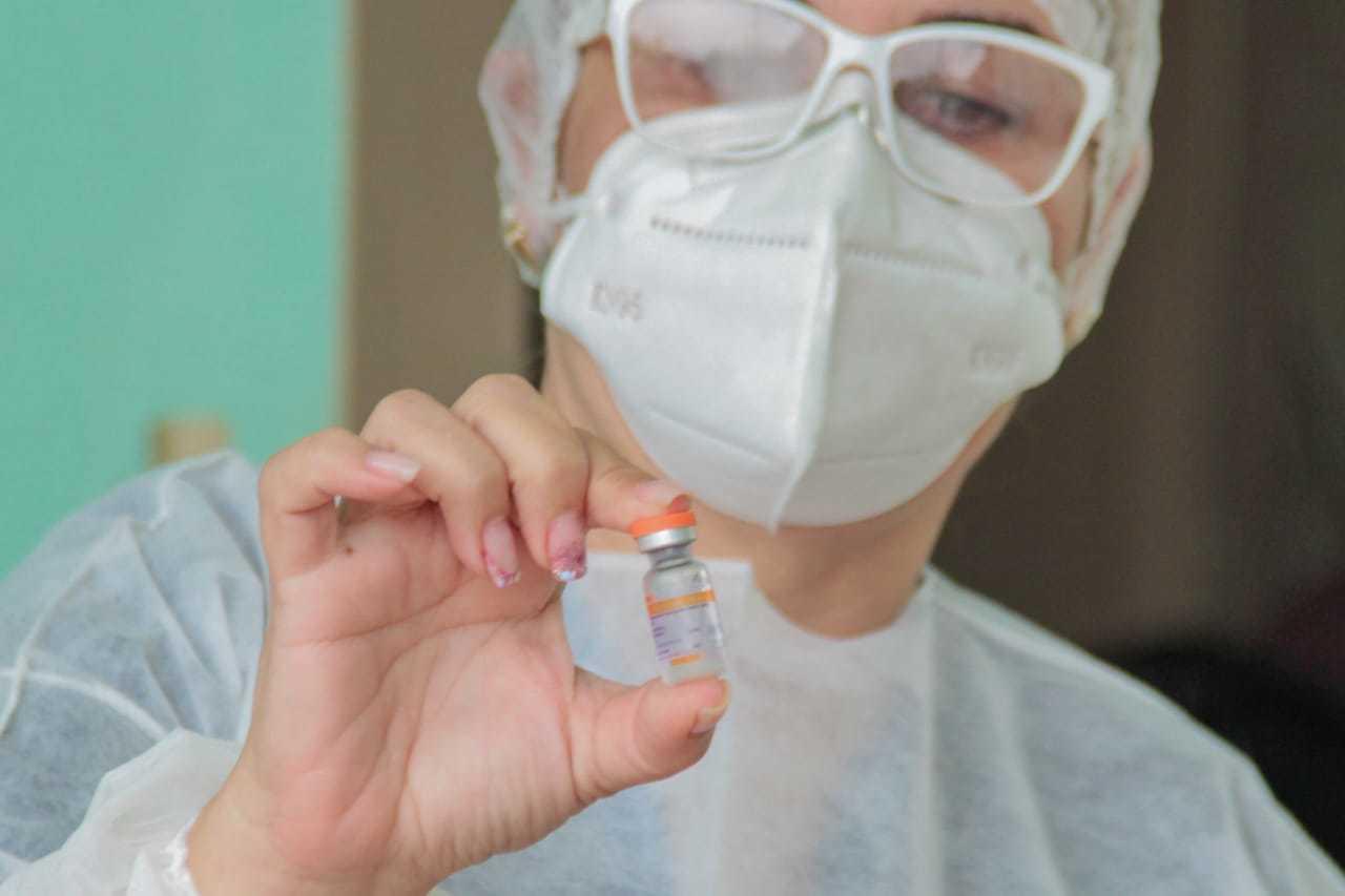 Funcionária da saúde segurando frasco da vacina coronavac. (Foto: Marcos Maluf)