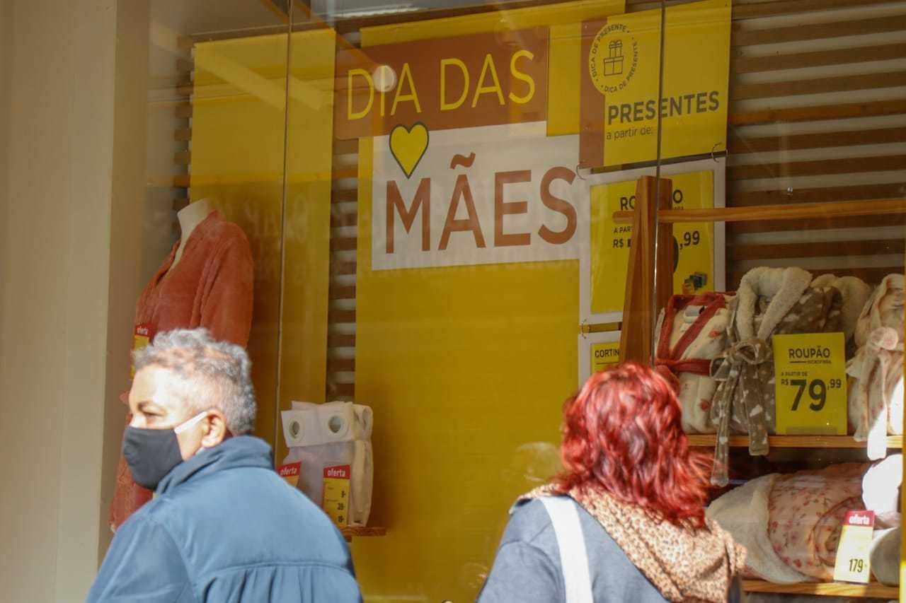 Pessoas ao lado de vitrine com anúncio sobre o Dia das Mães no Centro. (Foto: Henrique Kawaminami)
