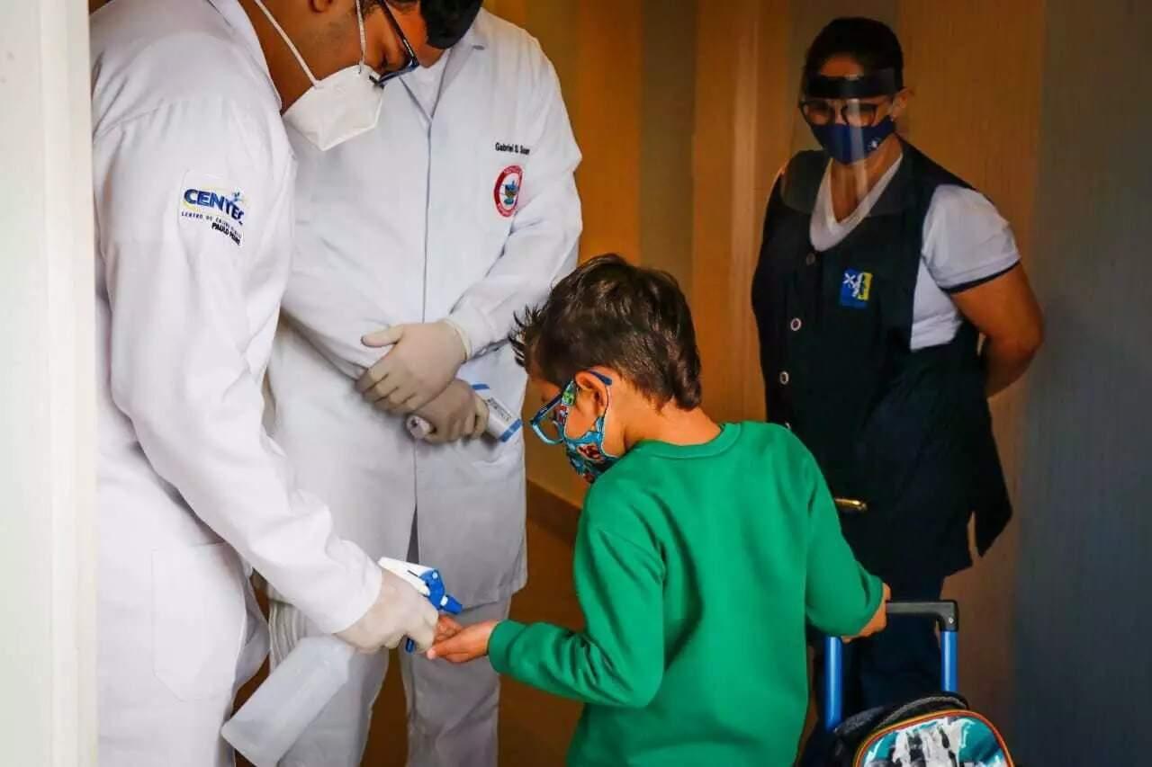 Criança higieniza as mãos ao chegar em escola particular em Campo Grande (Foto: Henrique Kawaminami/Arquivo)