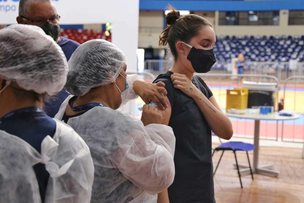 Jovem sendo vacinada no ponto montado no ginásio Guanandizão (Foto: Paulo Francis)