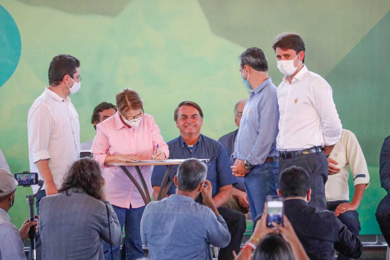 Bolsonaro, de camisa azul, sorri enquanto ministra Tereza Cristina, de camisa rosa, assina documento. (Foto: Henrique Kawaminami)