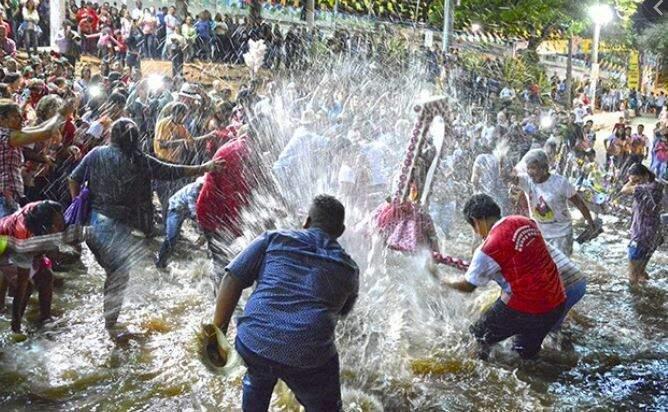 Momento em que fiéis dão banhos nos santos, no Rio Paraguai, (Foto: Diário Corumbaense)