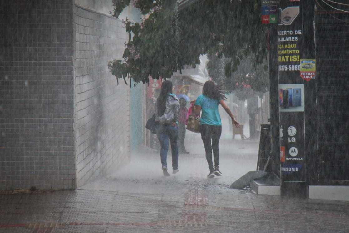 Mulheres na Capital correndo para se esconder da chuva. (Foto: Henrique Kawaminami)