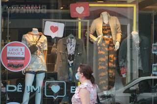 Mulher passa por vitrine de loja com promoção para o Dia dos Namorados (Foto: Marcos Maluf)