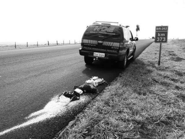 Veículo da PRF na pista, e cocaína apreendida com traficantes espalhada, depois de tiroteiro. (Foto: Arquivo/Diario Corumbaense)