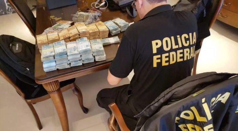 Policial federal conta pilhas de dinheiro em mesa. (Foto: Divulgação)