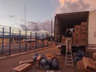 Policiais retirando as mercadorias de dentro da carroceria. (Foto: PRF)
