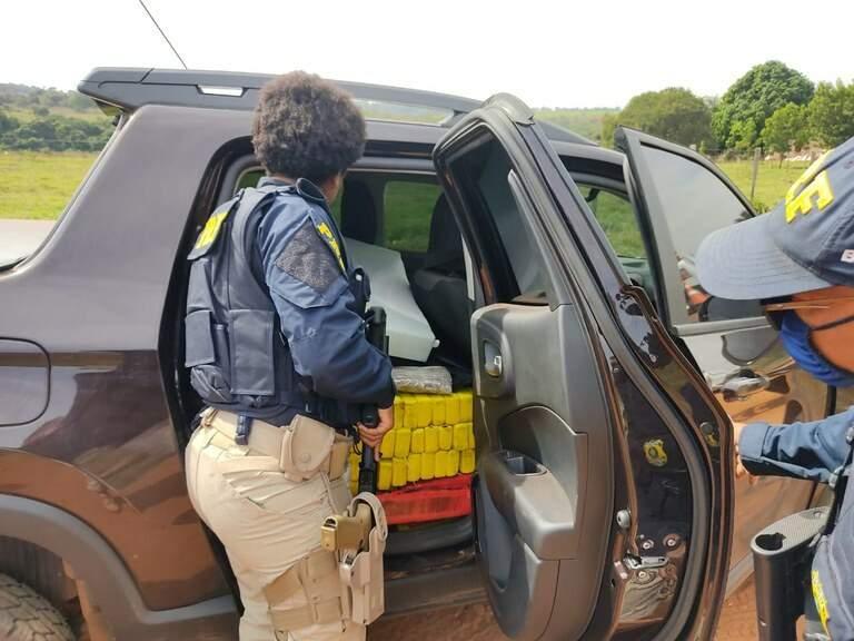 Policiais diante da carga de maconha encontrada no veículo. (Foto: PRF)