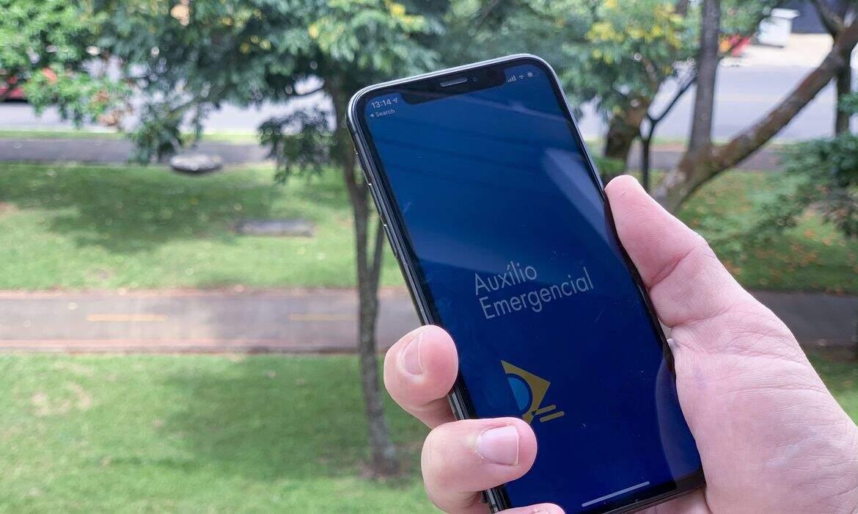 Beneficiário abre aplicativo do programa federal no celular (Foto: Agência Brasil)