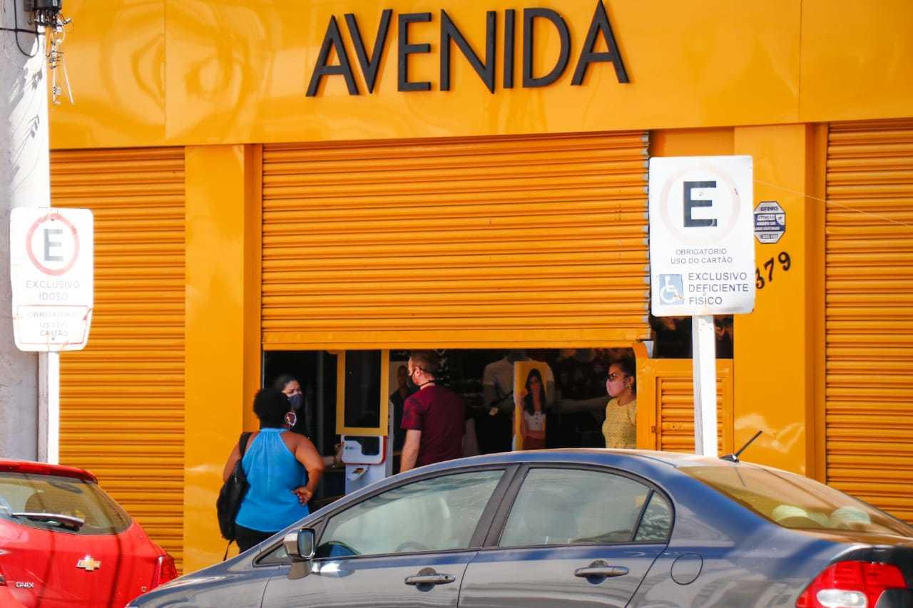 Loja funcionando com porta meia aberta em março (Foto: Henrique Kawaminami/Arquivo)