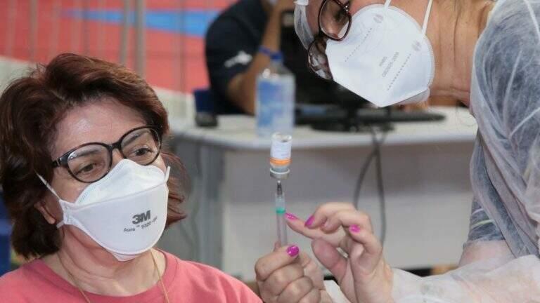 Profissional de saúde mostra dose de vacina em seringa para mulher (Foto: PMCG)