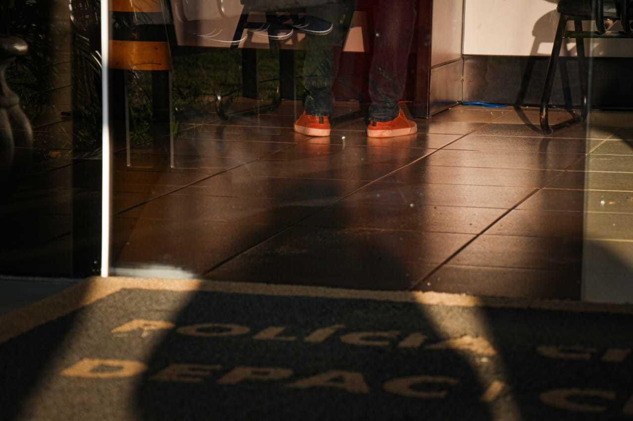 Em frente à delegacia, sombra do rapaz, que pediu para ter o nome preservado e contou detalhes das horas de terror à reportagem (Foto: Henrique Kawaminami)