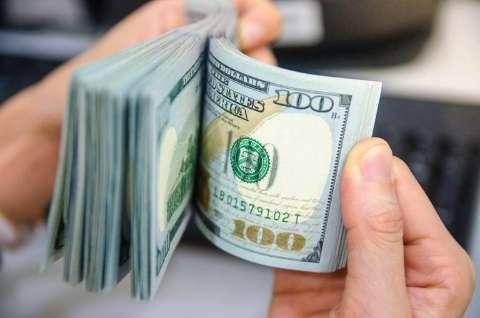 Dólar vira e cai a R$ 5,04 com fluxo e expectativa por Copom