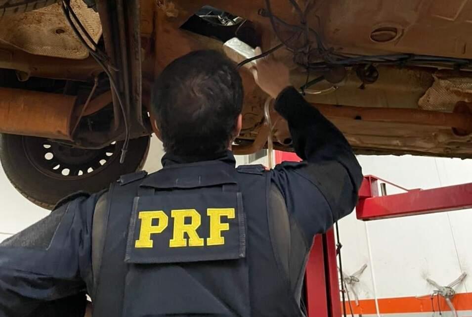 Policial retira tablete de pasta-base de assoalho de carro (Foto: Divulgação/PRF)
