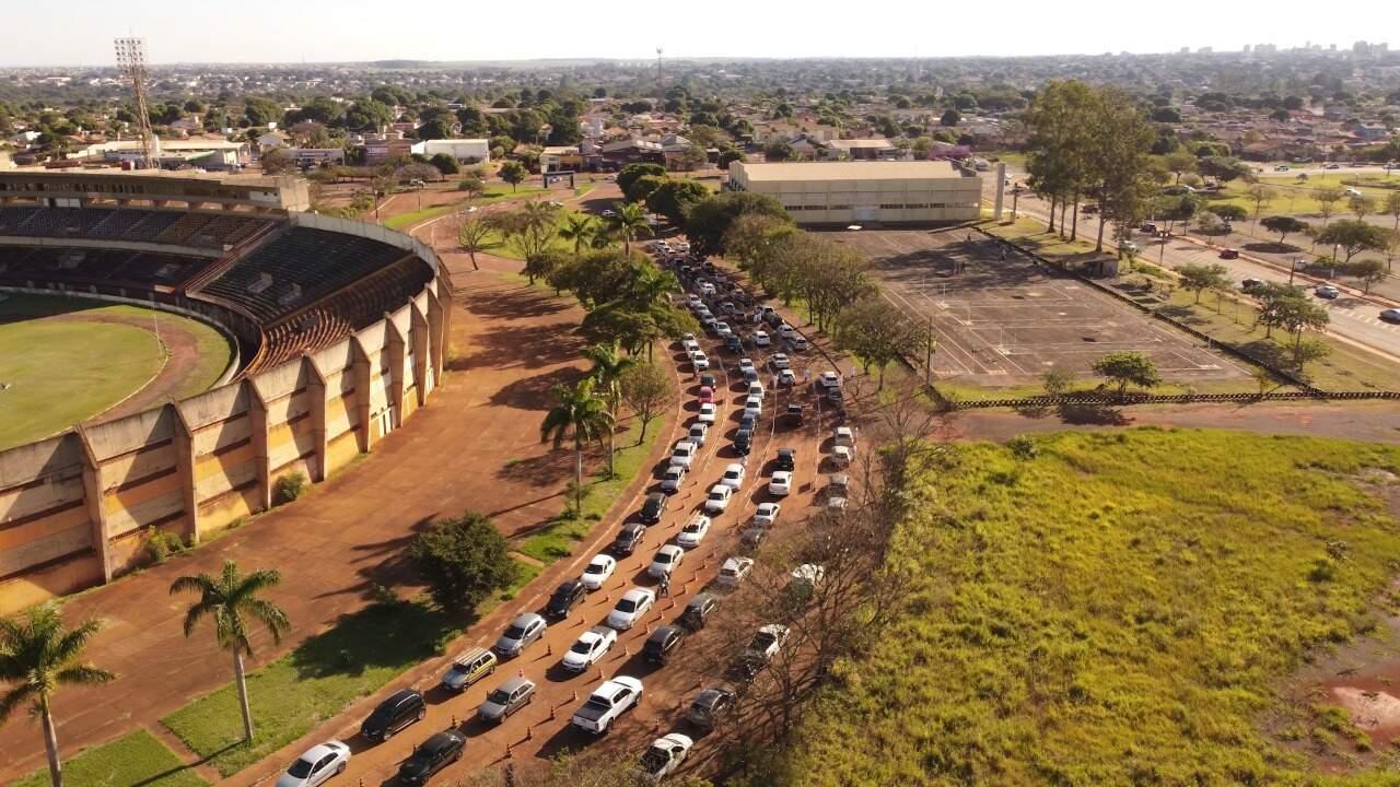 Fila de carros no drive-thru ao lado do estádio Douradão, nesta semana (Foto: Hallino Gomes)