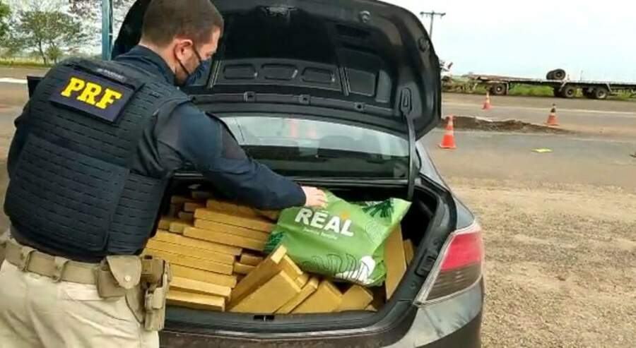 Tabletes de maocnha estavam no porta malas do automóvel. (Foto: PRF)