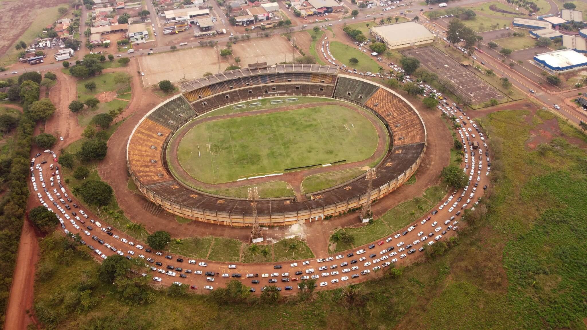 Fila de carros no entorno do estádio Douradão para acesso ao drive-thru da vacina (Foto: Hallinno Soares)