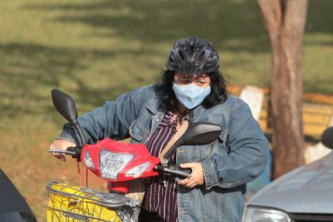 Para garantir vacina, Luciara encara frio e fila de drive em bicicleta elétrica