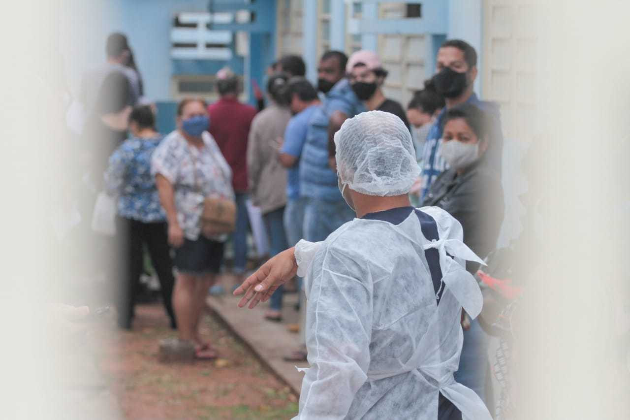 Profissional organiza fila em posto de saúde, para testagem na Capital. (Foto: Henrique Kawaminami)