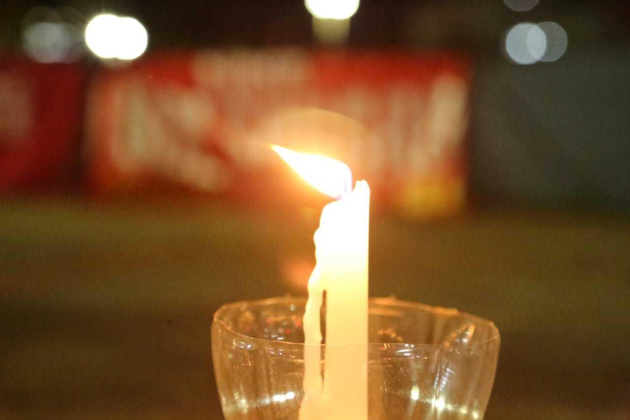 """Chama da vela permaneceu acesa nesta, contracenando com faixa de """"Fora Bolsonaro"""" ao fundo (Foto: Kisie Ainoã)"""
