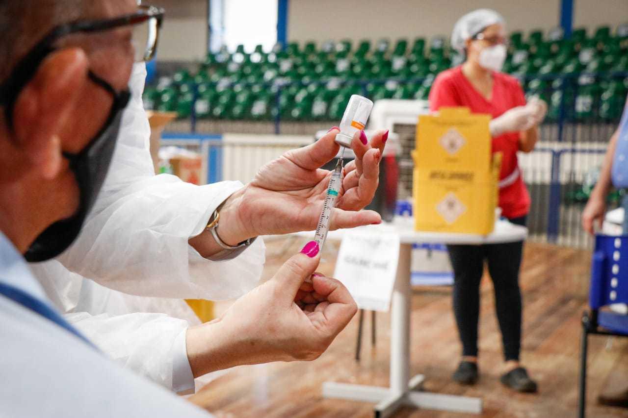 Dose da vacina contra a covid-19 nas mãos de uma servidora da saúde. (Foto: Henrique Kawaminami)