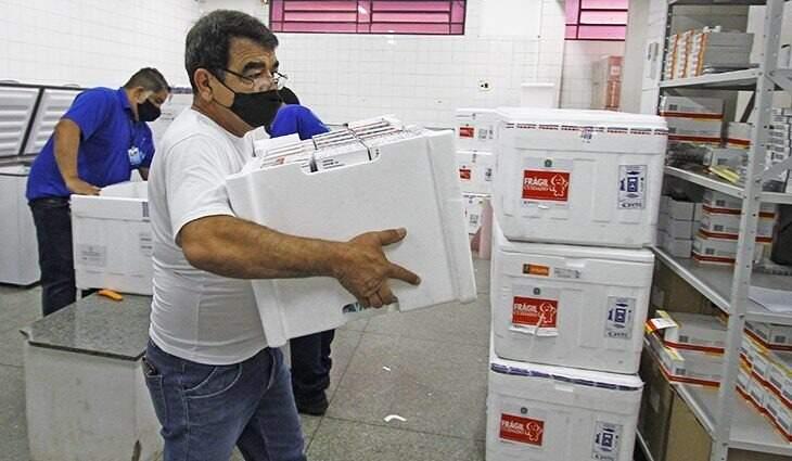Funcionários manipulam caixas térmicas contendo vacinas em central de distribuição (Foto: Governo de MS/Divulgação)