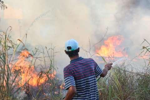 Em alerta com fogo, moradores tentam apagar chamas com mangueiras