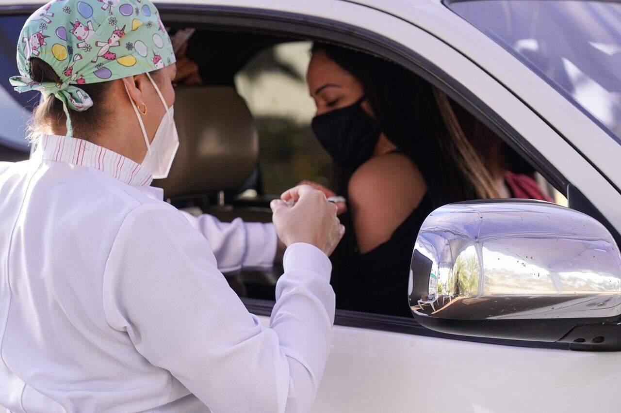 Moradora é vacinada em drive-thru montado em shopping de Pedro Juan (Foto: Divulgação)